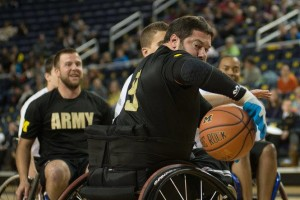 Playing for Army, TEAM USA Paralympic Track and Field Team member Scot Severn passes the ball behind his back in the 2014 Army-Navy Wheelchair Basketball Game at Crisler Center.