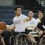 Navy team captain Jimmy Moceri looks for a teammate down court during the 2014 Army-Navy Wheelchair Basketball Game at Crisler Center. Playing for Army to Moceri's right, TEAM USA Paralympic Track and Field Team member Scot Severn jockeys for an intercept.